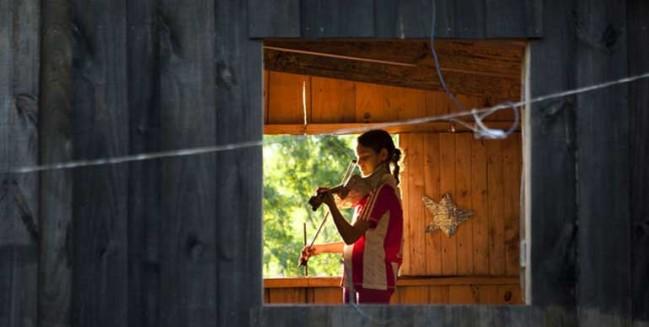 l'ochestra degli strumenti reciclati - ragazza suona il violino in una baraccopoli
