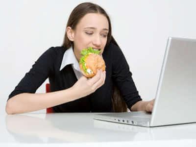 ragazza mangia al pc